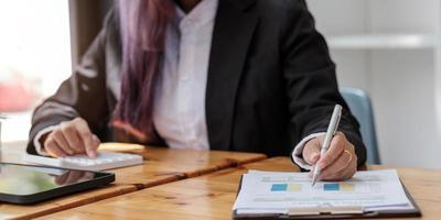 närbild av affärskvinna investeringskonsult analysera företagets årsredovisning balansräkningen arbetar med dokument grafer. konceptbild av ekonomin, marknadsföring foto