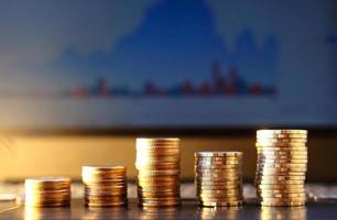 stack av mynt på bärbar dator och graf bakgrund och spara pengar och koncept för affärstillväxt foto