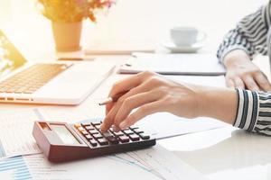 affärskvinna som använder en miniräknare och skriver anteckningar. skatter, besparingar, ekonomi och ekonomikoncept foto