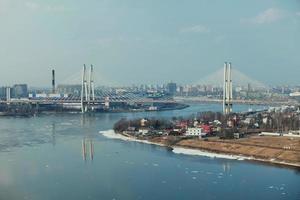 stadsbild med en kabelstannad bro över en bred slingrande flod foto