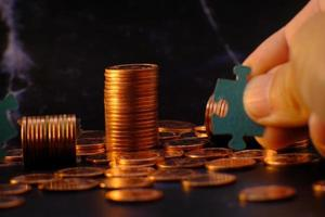 en person som håller en pusselbit bredvid en stapel mynt foto