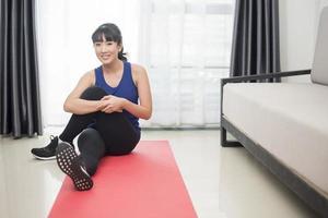 vacker ung sportig kvinna som sträcker sig hemma foto
