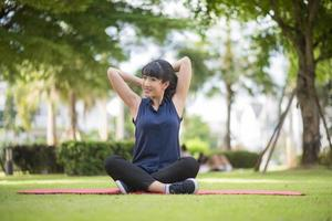 vacker yogakvinna på grön park foto
