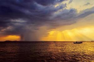 dramatisk solnedgång och kommande regnig storm till sjöss foto