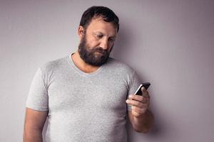 skäggig man i grå t-shirt som håller mobiltelefonen foto