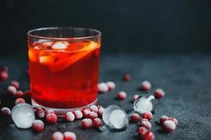 aperol spritz med is och tranbär på svart bakgrund. foto