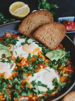 shakshuka med ägg, tomater, paprika och persilja i en kastrull. shakshuka är en traditionell israelisk mat. foto