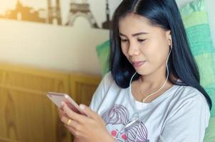 kvinna som spelar telefon på sängen sätta på hörlurar och lyssna på musik. asiatisk tjej foto