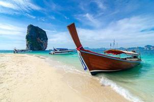 poda ö träbåt parkerad vid havet, vit strand på en klarblå himmel, blått hav foto