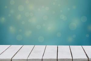blå bakgrund med selektiv inriktning. den gröna bakgrunden har ett bokehblad och gräs på ett vitt trägolv. tomt bord tomt utrymme träbord tomt foto