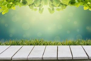 naturlig grön bakgrund med selektiv inriktning. den gröna bakgrunden har ett bokehblad och gräs på ett vitt trägolv. foto