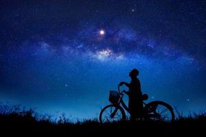 personen cyklar mitt i stjärnornas galax foto