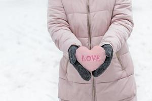 kvinnors händer i varma grå vantar med ett snöigt rosa hjärta. begreppet alla hjärtans dag. inskriptionen på hjärtat kärlek foto