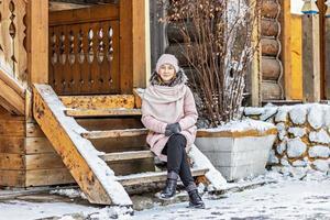 varmt klädd ung kvinna poserar på verandan i ett trähus i byn. vintersemester på landsbygden foto