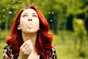 kvinna med röda hår blåser bort en maskros i parken foto
