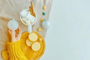 flickan håller julboll, kopp kakao, kakor och bordsduk på bordet. foto