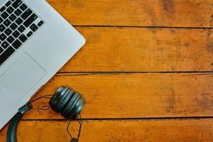 bärbar dator och trådlösa hörlurar på träbord. foto