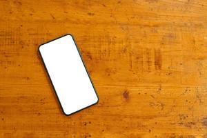 platt låg av mobiltelefon på träbord. foto