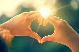 händerna på kvinnor och män är hjärtformen med solljuset som passerar genom händerna foto