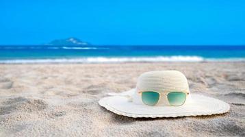 hattar och glasögon ligger på de havsblåa havsstränderna på en klar dag foto