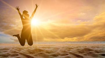 flickan hoppar med roligt på stranden, havet med den gyllene solen på kvällen. sommar koncept foto