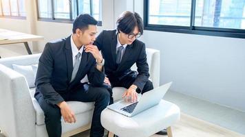 en grupp av två manliga affärsmän arbetar med datorer på allvar på kontoret. foto