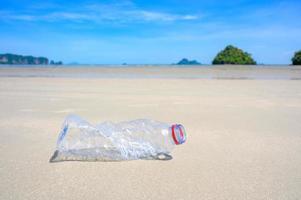 skräp stranden havet plastflaskan ligger på stranden och förorenar havet och livet i marint liv spillde skräp på den stora stadens strand. tomma begagnade smutsiga plastflaskor foto