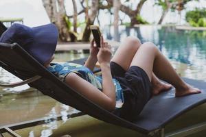 ung kvinna som bär hatt och casual outfit sitter på bänken nära poolen och använder smartphone för att ta foto under sommarsemester