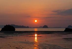 vacker solnedgång på stranden på sommaren med reflektion av solen i vattnet foto