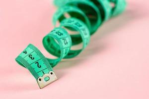 måttband. kropp som mäter lockigt linjal sy tyg skräddarsy mjuk tejp på rosa ros bakgrund. foto