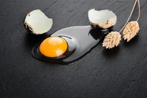 vaktelägg på svart stenbakgrund, trasigt, knäckt vaktelägg, äggula av vaktelägg. ekologisk produkt. foto