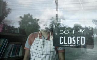 kvinnans butiksägare som hänger stängt skylt i ytterdörren till sin butik. effekt av koronavirus eller utbrott av covid-19 2020. foto