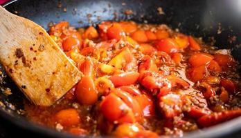 berömd mat i norra Thailand. huvudkomponenterna är tomater och fläsk. närbild av tomater i röd currypasta i panna. foto