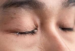 närbild av asiatisk kvinna som gråter av tår. foto