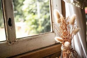 torkade blommor i en glasflaska på träbord vid fönstret med solskenet som kommer in i rummet. vardagsrumsdekoration. foto