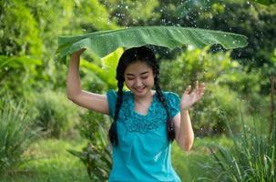 porträtt av en ung asiatisk kvinna med svart hår som håller ett bananblad i regnet på den gröna trädgårdsbakgrunden foto