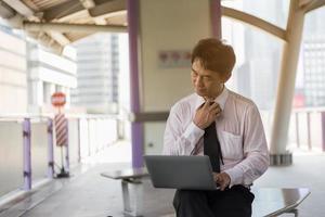asiatisk affärsman som arbetar på tågstationen foto