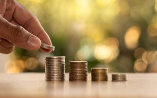 mänskliga händer som håller mynt och högar av mynt på trägolv ekonomiska och investeringsidéer. foto