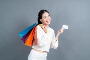 vacker asiatisk kvinna med kassar och visar kreditkort foto