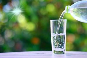 hälla renat färskt dricksvatten från flaskan på träbord och mineralvatten koncept foto