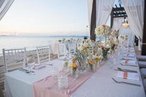 det eleganta middagsbordet på stranden foto