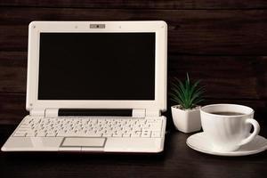 arbetsplats hemma. bärbar dator och kaffekopp på träbakgrund. plats för text. foto