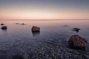 abstrakt solnedgång på Egeiska havet med suddig rörelse vatten, kassandra, Grekland. foto