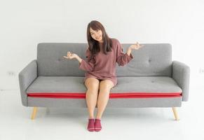 asiatisk kvinna på soffan i vardagsrummet med kopieringsutrymme foto