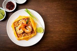 thailändska stekta nudlar med räkor och äggpaket foto