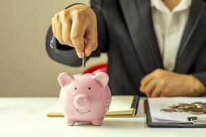 sparande och finansidéer. affärsmän lägger in pengarmynt i en spargris för att spara pengar och planera sin ekonomi. foto
