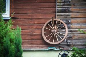stort gammalt trähjul som hänger på träplankväggen i ett lantligt hus foto