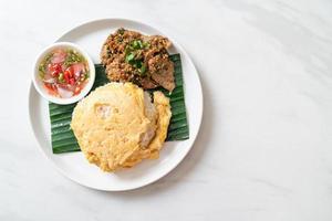 ägg på toppat ris med grillat fläsk och kryddig sås - asiatisk matstil foto