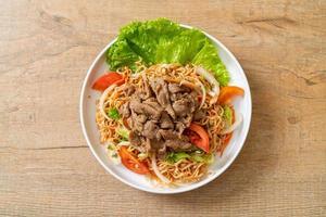 snabb nudel kryddig sallad med fläsk på en vit platta - asiatisk matstil foto