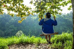 baksida av flicka på gunga vid campuhan åsen promenad i ubud i bali foto